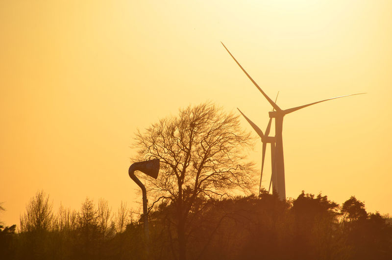 Low angle view of windmills against clear sky during sunset