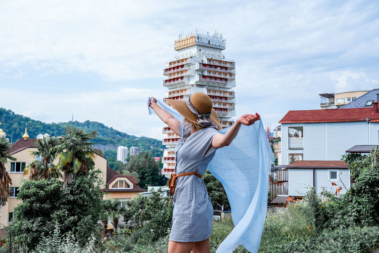 Woman standing against building and sky