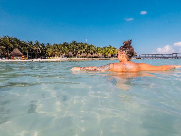 Rear view of woman swimming in sea against sky