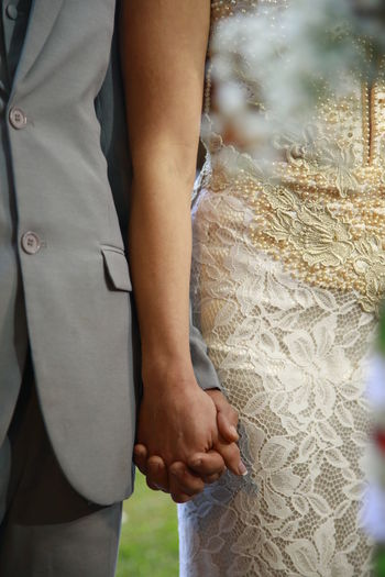 Close-up of hands and woman standing outdoors