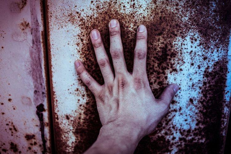 Man's hand touching rusty wall