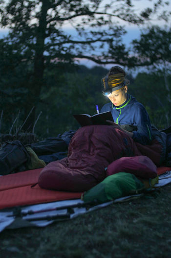 caucasian female hiker reading book/writing journal at night while wildcamping, strong light from headlamp Backpacking Camping Headlamp Hiking Light Reading Travel Trekking Woman Writing Adventure Beam Book Caucasian Child Childhood Concentration Day Evening Female Forest Full Length Hobby Journal Land Leisure Activity Lifestyles Males  Men Nature Night One Person Outdoors People person Plant Real People Sitting Sleeping Sleeping Bag Tree Warm Clothing