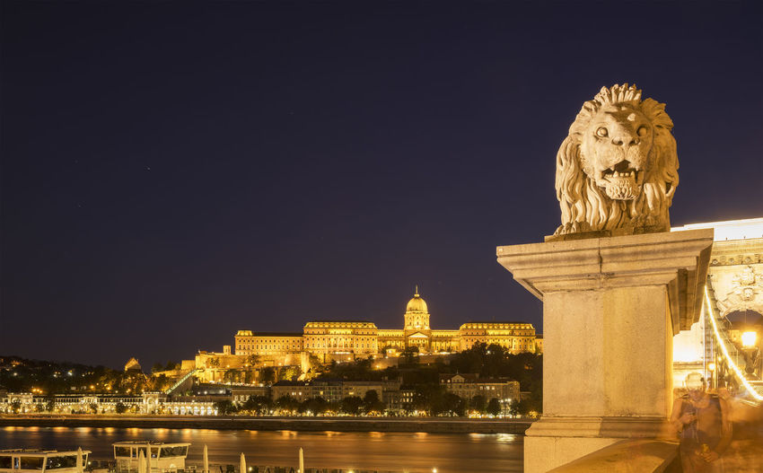 Statue on budapest waterfront against clear sky at night