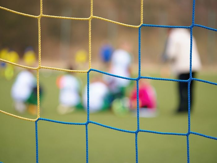 Football gate net. soccer gate net. in blurry background stand players. training of junior team.