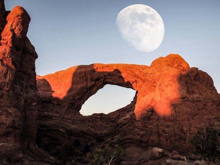 Low angle view of natural arch against moon