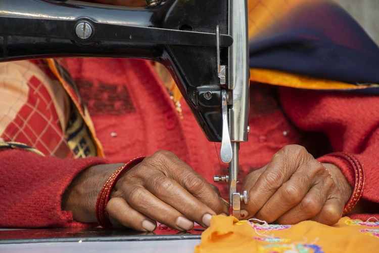 Close-up of hands working with sewing machine