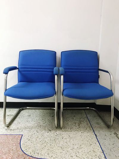 Empty chair against blue wall