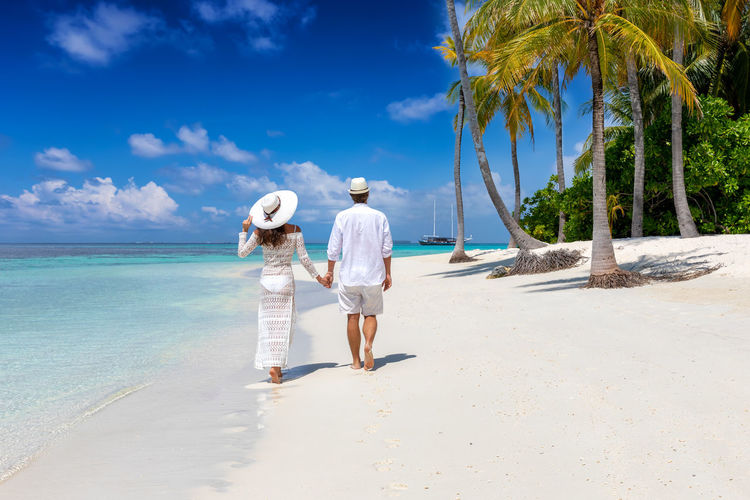 Traveler couple in white summer clothes walks along a tropical paradise beach with palm trees and turquoise sea Water Land Sea Real People Sky Beach Women Full Length Rear View Two People Adult Tree Nature Leisure Activity Togetherness Positive Emotion Lifestyles Couple - Relationship Walking Palm Tree Tropical Climate Paradise Turquoise Colored Blue Sky Island Vacations Honeymoon Maldives Caribbean White Hat Dress Fashion Elegant Travel Traveler Tourism Tourist