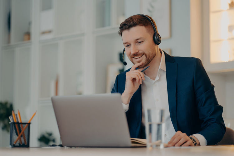 Smiling man using mobile phone while sitting on table