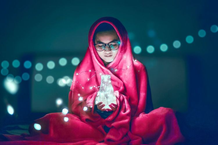 Young woman wrapped in blanket holding jar with illuminated string light at home