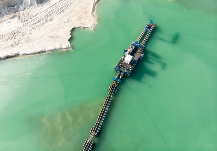 Aerial view of the long boom of a suction excavator in a quartz quarry for the excavation of white sand. Construction Cutting Quartz Suction Trailing Aerial Aerial View Cutting Tool Dike Dredge Equipment Excavation Geology Germany Lake Mineral Mining Outdoor Quarry Silt Water White