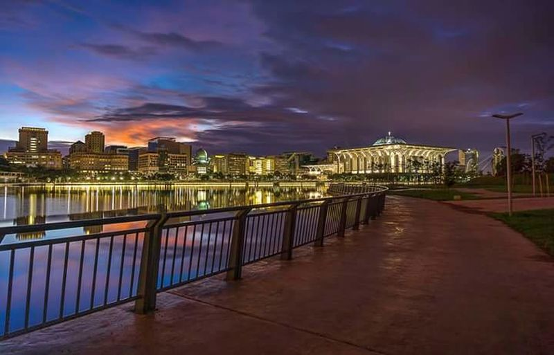 City lit up against cloudy sky