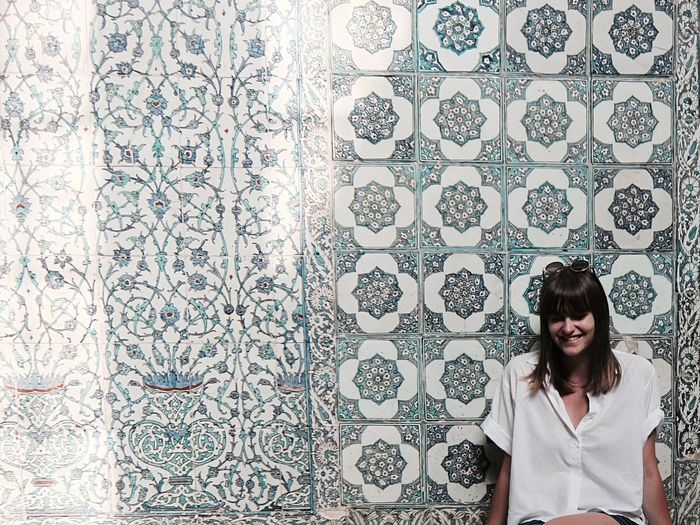 Happy woman against mosaic wall at topkapi palace