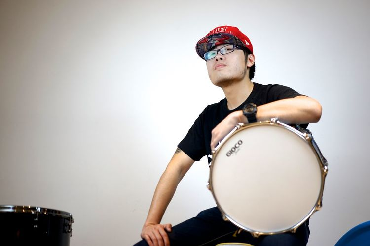 Asian  Studio Adult Arts Culture And Entertainment Chinese Contemplation Drum - Percussion Instrument Drumstick Hairstyle Indoors  Lifestyles Looking Music Musical Equipment Musical Instrument Musician One Person Portrait Purple Rock Music Sitting Studio Shot Waist Up White Background Young Adult