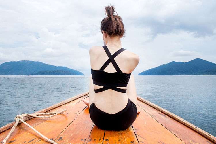 Rear view of woman sitting in sea against sky