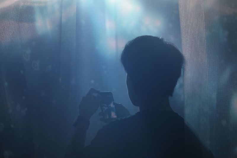 Rear view of man photographing through mobile phone amidst curtains