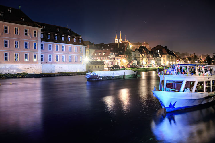 Boats Moored On River By Illuminated Buildings In City At Night