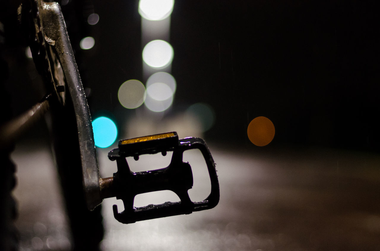 Cropped image of bicycle pedal at night