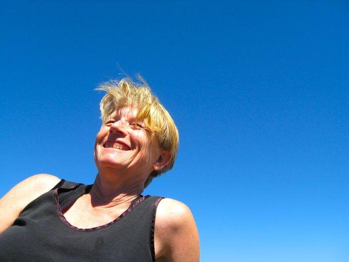 Smiling Mature Woman Against Blue Sky