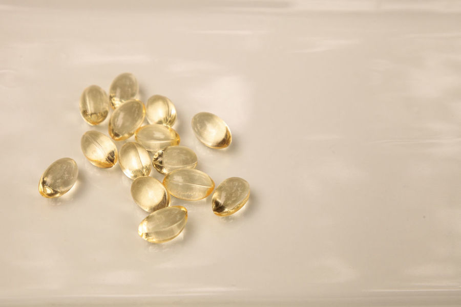 Gold gel capsule of vitamin E displayed on a white surface. Medicine Gel Caps Gel Capsules Gelatin Capsules Gold Capsules Health Healthy Eating Liquid Pills Liquid Tablets Nutrition Nutritional Supplement Skin Health Vitamin Vitamin E Yellow Pills