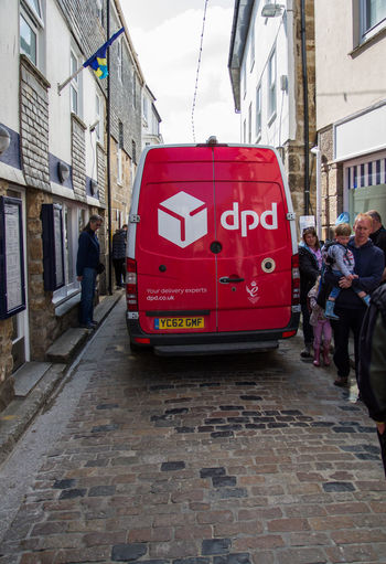 A red delivery van from the logistics and parcel delivery company DPD squeezing slowly along a small cobbled street in St Ives, Cornwall, UK. Adult Architecture Building Exterior Built Structure Business City Cobbled Streets Day Delivering Delivery Service Delivery Van Dpd Full Length Land Vehicle Lifestyles Logistics Men Mode Of Transport Outdoors People Real People Red Transportation Walking Women