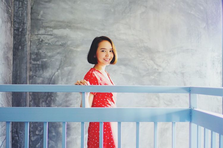 Portrait of smiling woman standing by railing against wall