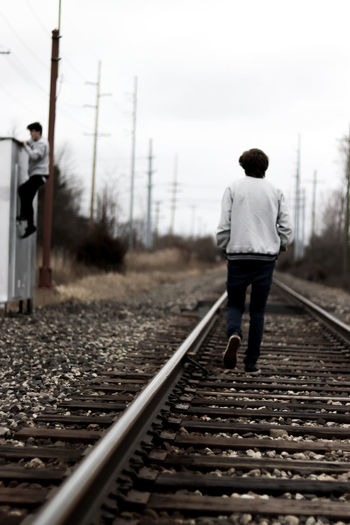 Bokeh Casual Clothing Clear Sky Day Full Length Lowsaturation One Person Outdoors Portrait Public Transportation Rail Transportation Railroad Railroad Tie Railroad Track Railway Track Real People Rear View Sky Standing The Way Forward Transportation Tree