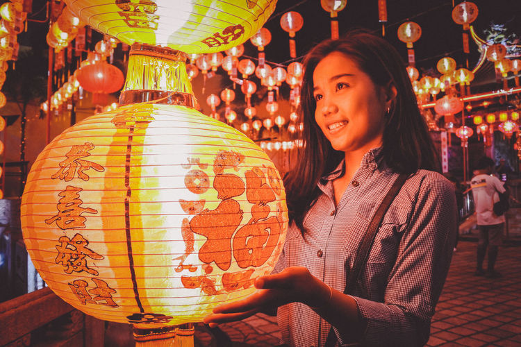 Young woman looking at illuminated lantern during night