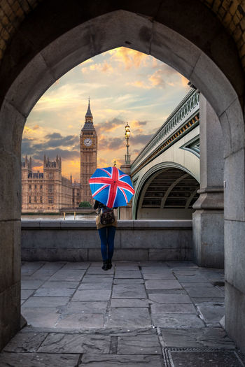 Woman standing against big ben seen through archway