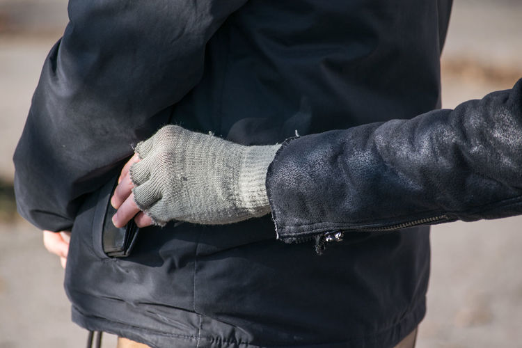 A white Caucasian man with gloves steals black wallet from a mans jacket pocket while he is standing in a line. Midsection Real People Men People Human Hand Focus On Foreground Hand Human Body Part Day Standing Front View Holding Casual Clothing Black Color Close-up Clothing Adult Outdoors Finger Wallet Thief Poverty Poor  Criminal Pick Pocket