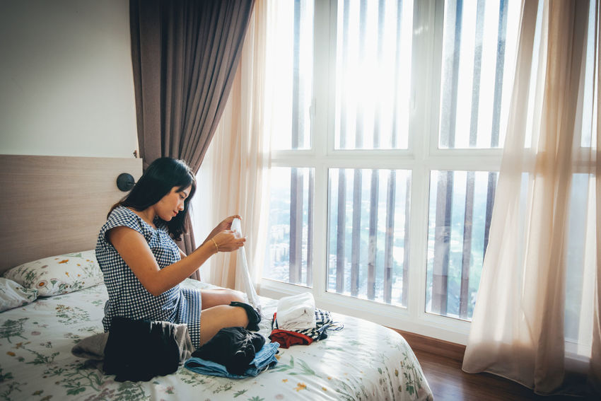 One Person Sitting Real People Window Curtain Lifestyles Indoors  Casual Clothing Furniture Leisure Activity Home Interior Full Length Day Young Adult Domestic Room Young Women Women Side View Adult Hairstyle