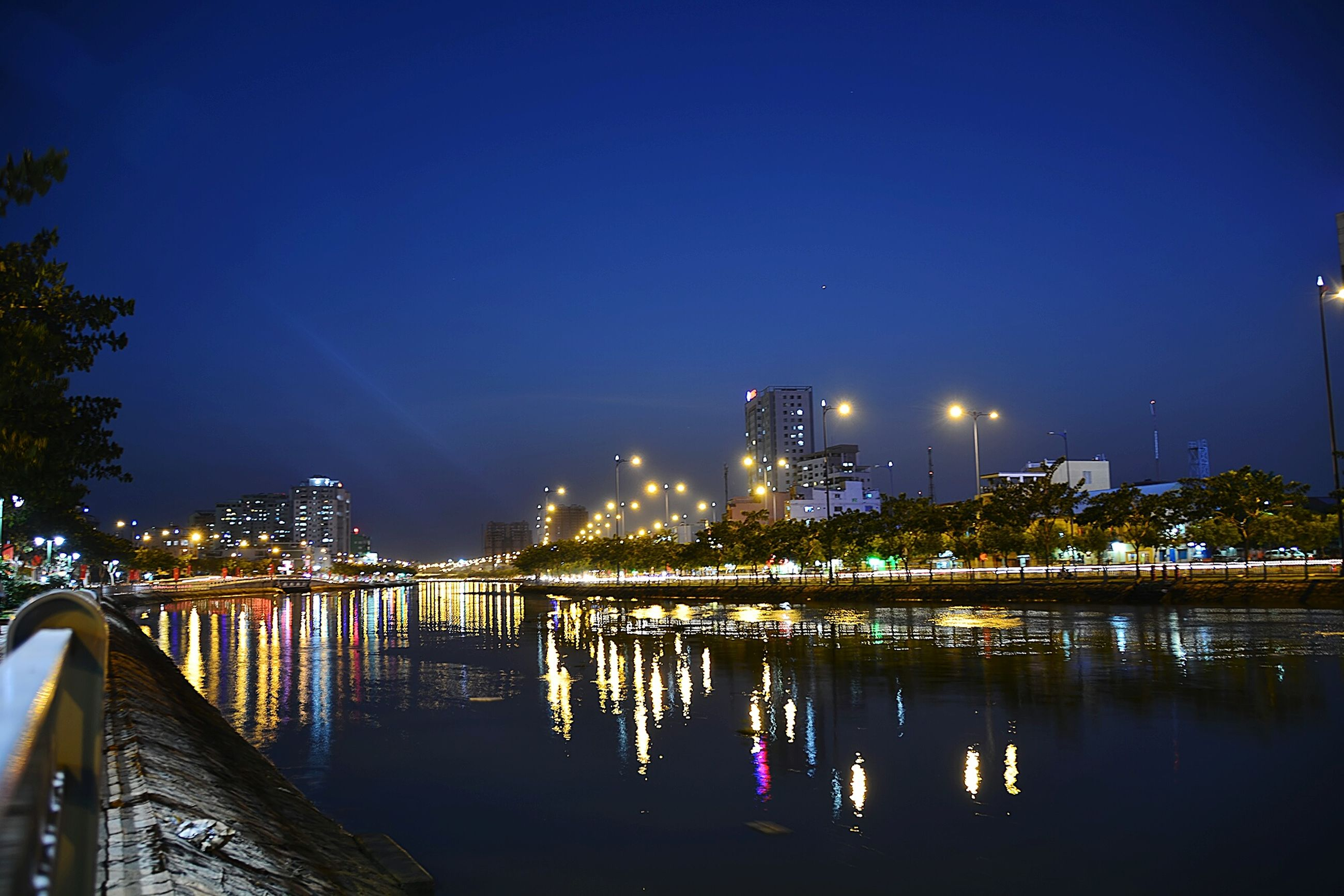 illuminated, night, water, reflection, architecture, built structure, clear sky, building exterior, city, river, blue, waterfront, copy space, sky, street light, lighting equipment, connection, bridge - man made structure, outdoors, light - natural phenomenon