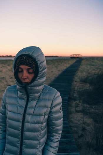 Portrait of woman standing in snow against sky during sunset