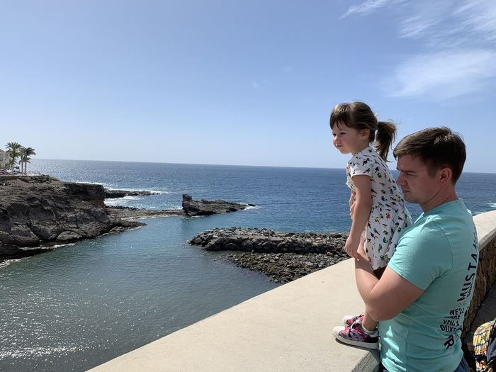 Man with daughter looking at sea