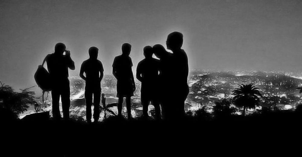 Silhouette men standing against sky
