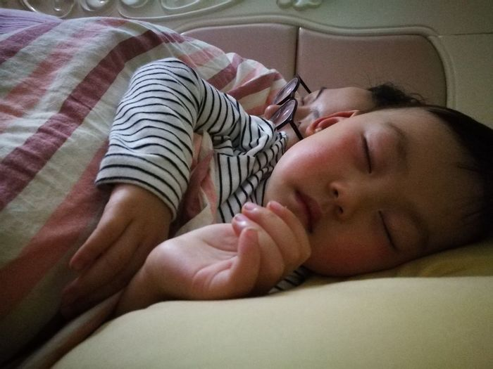 Midsection of baby sleeping in bed