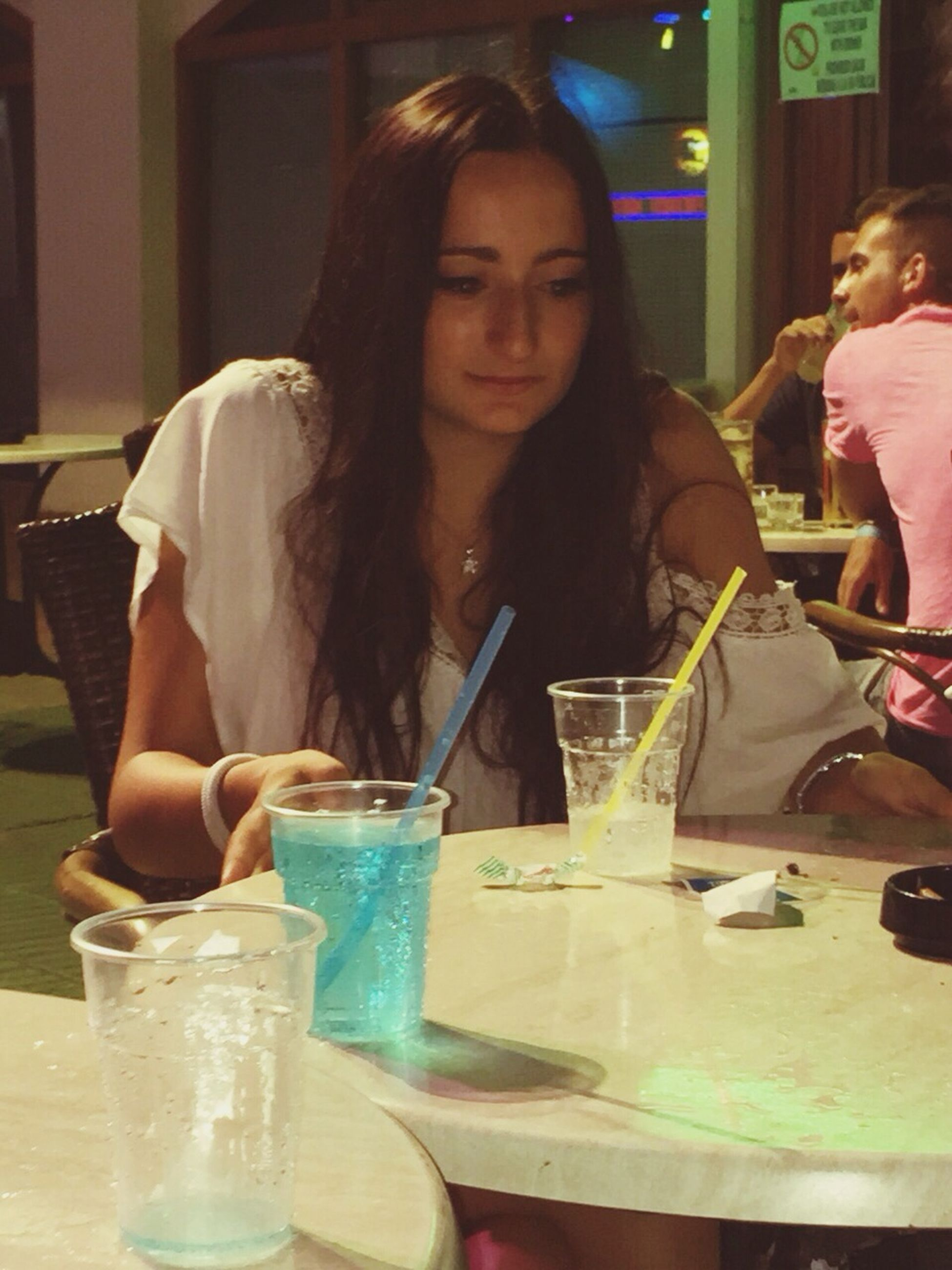 person, lifestyles, young adult, indoors, casual clothing, food and drink, leisure activity, drink, young women, sitting, front view, holding, portrait, restaurant, waist up, looking at camera, refreshment, headshot