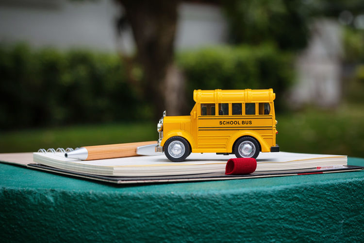 Close-up of toy school bus on book