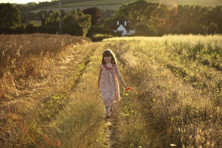 FULL LENGTH OF CUTE GIRL WALKING ON SUNNY FIELD
