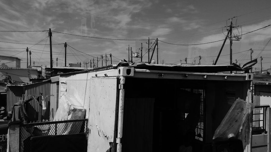 EyeEmNewHere Informal SettlementInformal Trading Cable Cloud - Sky Outdoors Built Structure Telephone Line Architecture Sky Informal Architecture Cold Cape Town Day Business Finance And Industry No People Building Exterior Electricity Pylon Prison Black And White Friday
