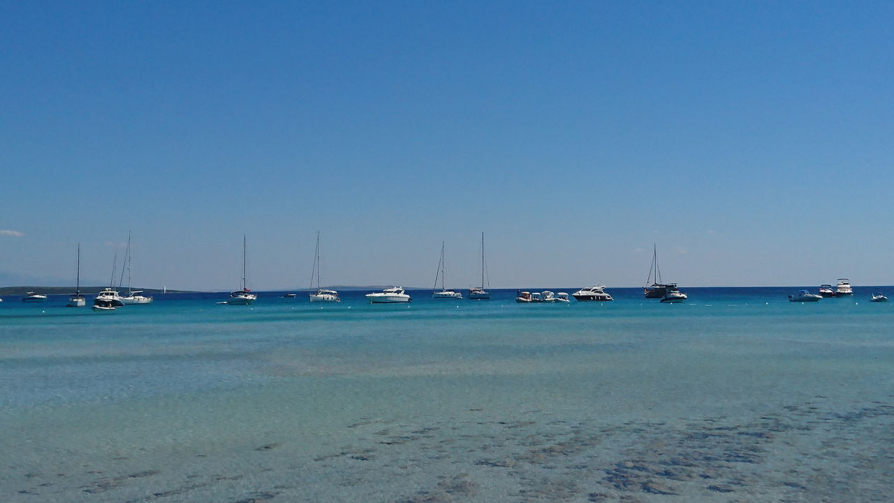 SAILBOATS MOORED ON SEA AGAINST CLEAR SKY