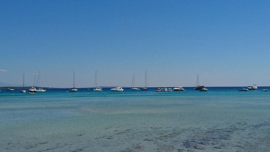 Sailboats moored on sea against clear blue sky