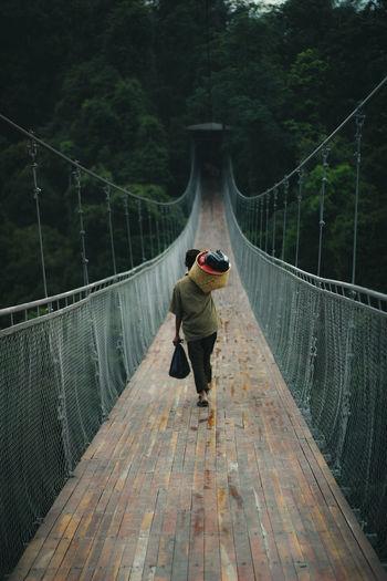 Rear view of boy walking on footbridge