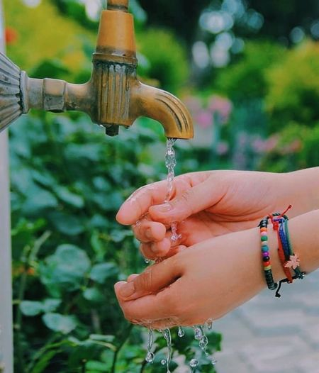 Close-up of woman hand holding faucet against blurred background