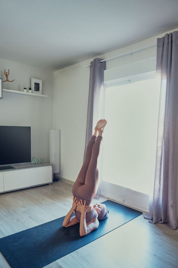 Woman with arms raised on floor at home