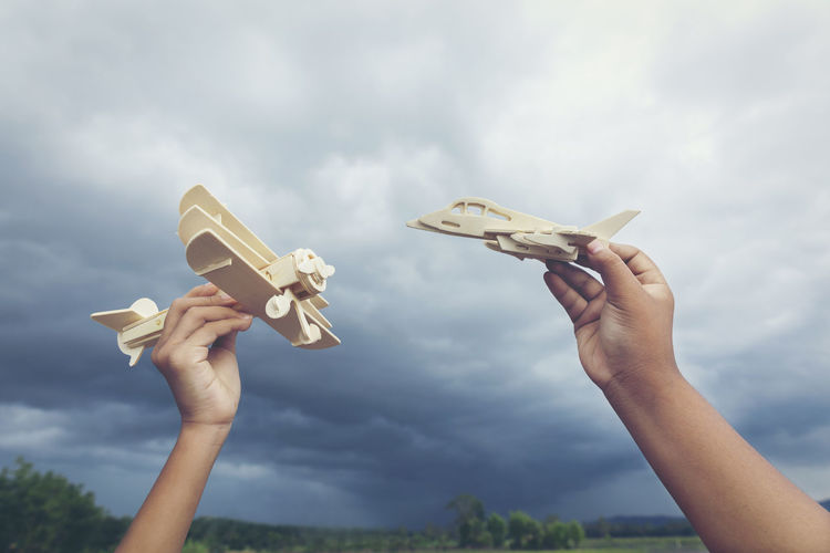 Cropped hands of people holding model airplane against cloudy sky