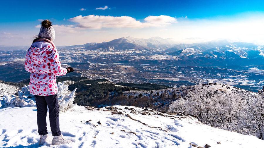 Girl standing on snowcapped mountain against sky