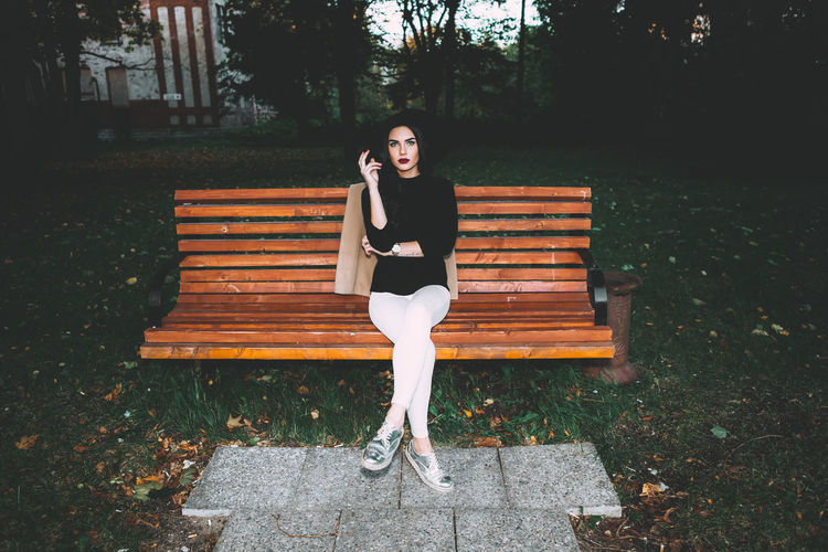 Full length of young woman sitting at park