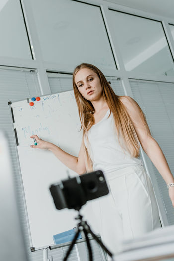 Young woman teaching students over video call