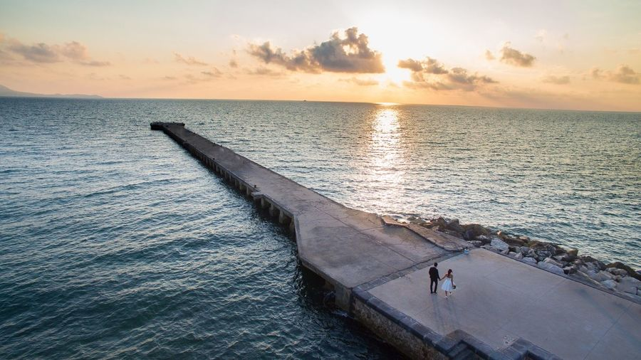 High angle view of couple walking on pier by sea against sky during sunset